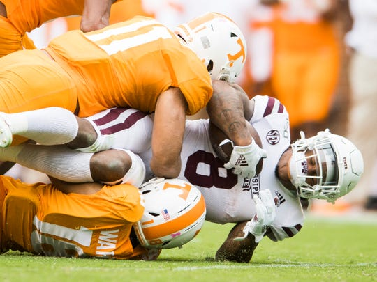 Tennessee linebacker Henry To'o To'o (11) and Tennessee defensive back Nigel Warrior (18) take down Mississippi State running back Kylin Hill (8) during Tennessee's home game against Mississippi State at Neyland Stadium on Saturday, October 12, 2019.