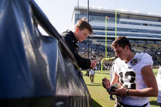 Purdue quarterback Jack Plummer (13) signs a young fan's football after defeating Maryland, 40-14, Saturday, Oct. 12, 2019 at Ross-Ade Stadium in West Lafayette.