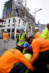 Workers are helped after a large portion of a hotel under construction suddenly collapsed in New Orleans on Saturday, Oct. 12, 2019. Several construction workers had to run to safety as the Hard Rock Hotel, which has been under construction for the last several months, came crashing down.