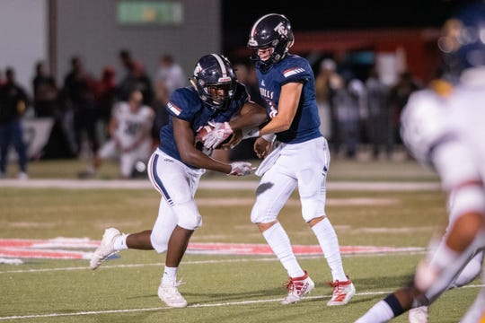 Teurlings Catholic's Sammy Leblanc (6) hands off the ball to TyRick Gary (10) during the play as the Teurlings Catholic Rebels take on the Carencro High Bears on Friday, Oct. 11, 2019.