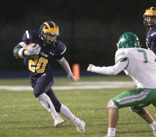 Hartland's Gage DeLanoy runs past Alex Vargas of Novi in the first quarter of the Eagles' 14-0 victory on Friday, Oct. 11, 2019.
