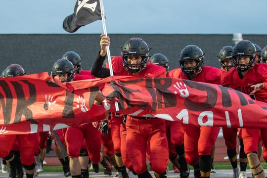 Led by flag-waving quarterback Joe Bona, Pinckney's football players take the field for a game against Dexter on Friday, Oct. 11, 2019.