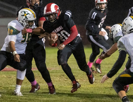 Manual running back Deaaron Robinson (20) finds a hole in the St. X line, Friday, Oct. 11, 2019 in Louisville Ky. A cold, rainy game meant lots of yardage on the ground for both teams.