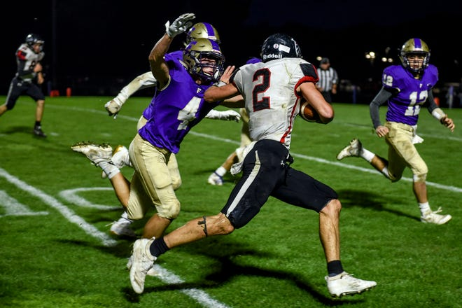 Fowlerville's Kaleb Chappell, left, tackles St. Johns' Brock Miller on a run during the second quarter on Friday, Oct. 11, 2019, at Fowlerville High School.