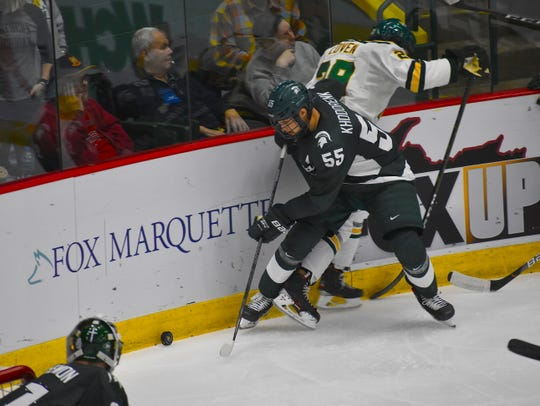 Michigan State's Patrick Khodorenko battles Northern Michigan's Grant Loven along the boards behind the Spartans net during the second period of Friday's game in Marquette. MSU won, 5-3.
