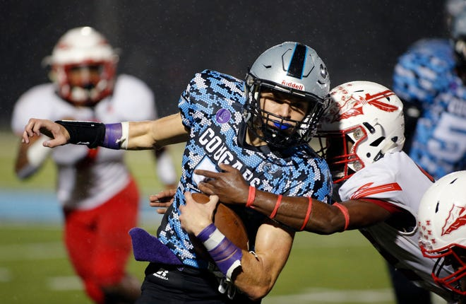 Lansing Catholic's Alex Watters, left, makes a gain against Sexton's Dontel Wright, Friday, Oct. 11, 2019, in Lansing, Mich. Lansing Catholic won 25-0.