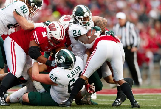 Oct 12, 2019; Madison, WI, USA; Michigan State Spartans running back Elijah Collins (24) is tackled with the football during the third quarter against the Wisconsin Badgers at Camp Randall Stadium. Mandatory Credit: Jeff Hanisch-USA TODAY Sports
