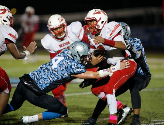 Sexton quarterback Amonte Douglas, right, is stopped by Lansing Catholic's Sam Edwards (4), Friday, Oct. 11, 2019, in Lansing, Mich. Lansing Catholic won 25-0.