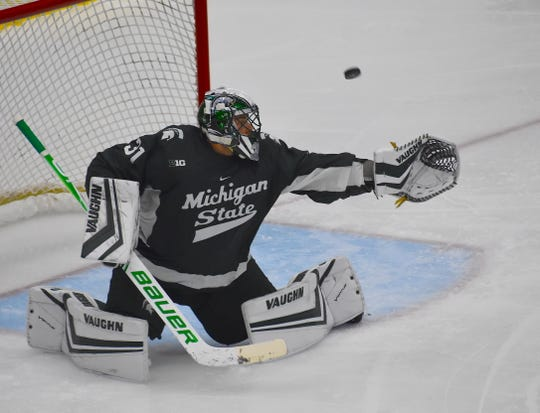 Michigan State goalie John Lethemon deflects an Northern Michigan shot into the netting during the second period of Friday's game in Marquette. MSU won its season opener, 5-3.