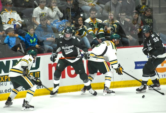Michigan State's Cole Krygier (8) battles Northern Michigan's Joe Nardi (left) and Darien Craighead along the boards, while MSU teammate Patrick Khodorenko looks on during the second period of Friday night's game in Marquette. MSU won, 5-3.