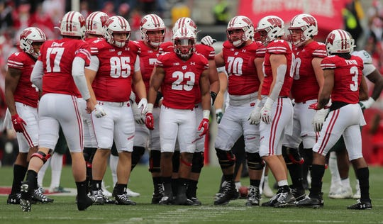 The Badgers offense waits to hear the play from quarterback Jack Coan (17) during the first half against Michigan State.