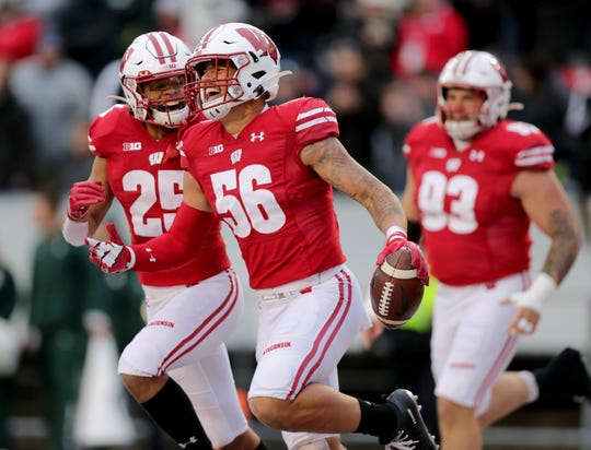 UW defensive players Zack Baun (56) and Eric Burrell are all smiles after Baun returned an interception 34 yards for a touchdown against Michigan State.