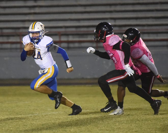 Mountain Home's Lawson Stockton tries to escape two Jacksonville defenders during the Bombers' 22-7 loss to the Titans on Friday night.