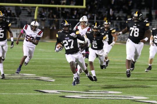 Running back Timothy Byrd (27) runs through Franklin Parish in Neville's 41-0 win on Friday night at Bill Ruple Stadium.