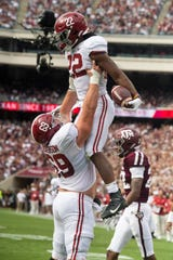 Alabama running back Najee Harris (22) is lifter by Alabama offensive lineman Landon Dickerson (69) after scoring a touchdown against Texas A&M at Kyle Field in College Station, Texas on Saturday October 12, 2019.