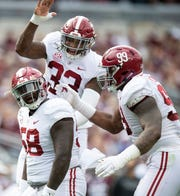 Alabama defensive lineman Christian Barmore (58) , linebacker Anfernee Jennings (33) and defensive lineman Raekwon Davis (99) celebrate Barmore's sack against Texas A&M at Kyle Field in College Station, Texas on Saturday October 12, 2019.
