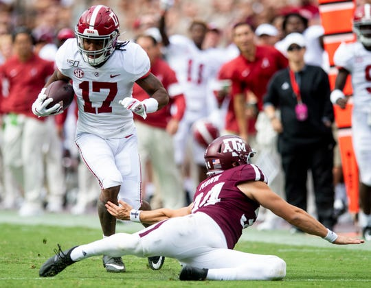 Alabama wide receiver Jaylen Waddle (17) makes a defender miss as he carries against Texas A&M at Kyle Field in College Station, Texas on Saturday October 12, 2019.