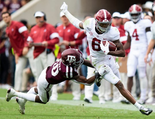 Alabama wide receiver DeVonta Smith (6) eludes Texas A&M defensive back Myles Jones (10) at Kyle Field in College Station, Texas on Saturday October 12, 2019.