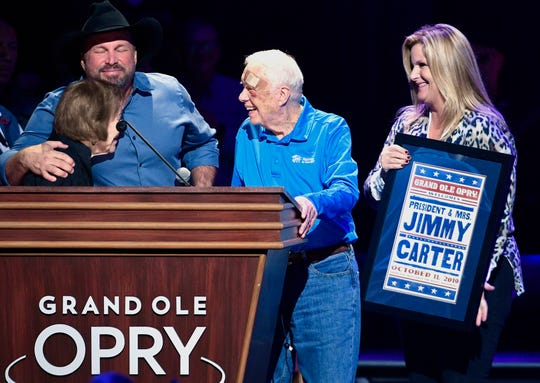 Garth Brooks and Trisha Yearwood introduce former President Jimmy Carter and Rosalynn Carter at the Grand Ole Opry on Friday.