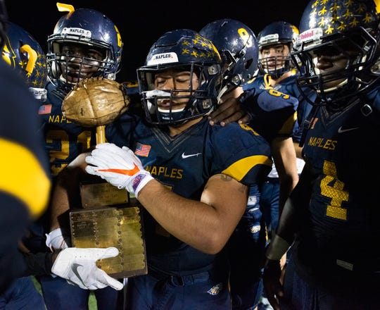 Elan Sommala of Naples celebrates with his teammates and the Coconut Bowl trophy after defeating Lely at Naples High Friday night, October 11, 2019.