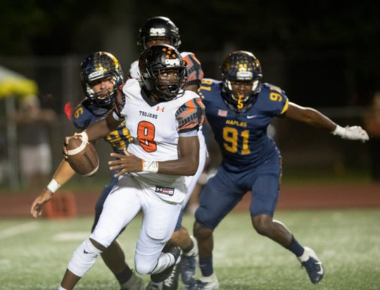 Lely quarterback Jeremiah Dervil tries to escape the  Naples defense during the game at Naples High Friday night, October 11, 2019.