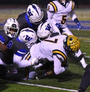 South Lyon Lion Mitch Komorous is tackled by a bunch of Walled Lake Western Warriors.