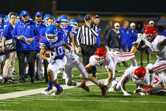 Catholic Central's Jonathan Brewer escape Orchard Lake St. Mary's defenders and runs down the field.