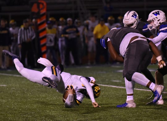 Walled Lake Western defensive lineman Justin Collier, left, thorws South Lyon QB Connor Fracassi for a loss - preventing him from picking up a short fourth-and-1 late in the first half.