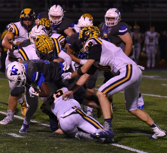 The South Lyon defense works together to bring down a Warrior runner.