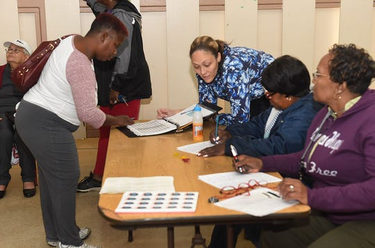 Voting commissioers sign in voters Saturday morning at the old Southwest Elementary School.