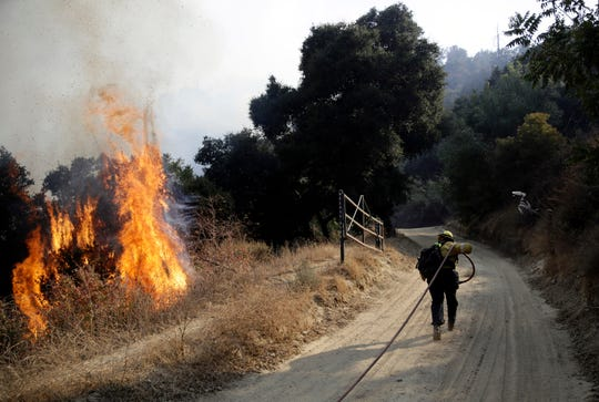 A firefighter runs up a fire road to hose down flames from a wildfire Saturday, Oct. 12, 2019, in Newhall, Calif. Los Angeles Fire Department spokesman Brian Humphrey said the bulk of the fire at the city's edge had moved away from homes and into rugged hillsides and canyons where firefighters were making steady progress slowing its advance.