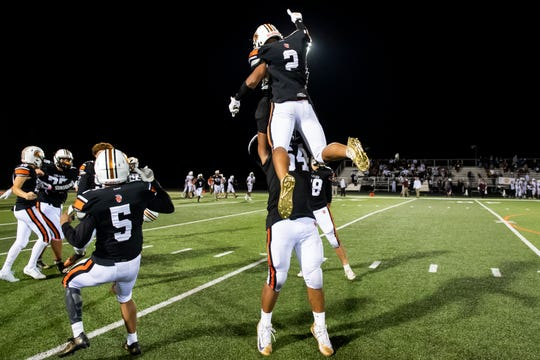 York Suburban's Devante Banks lifts up Savion Harrison after the Trojans defeated Gettysburg 30-19 during a YAIAA Division II football game in Spring Garden Township on Friday, October 11, 2019.