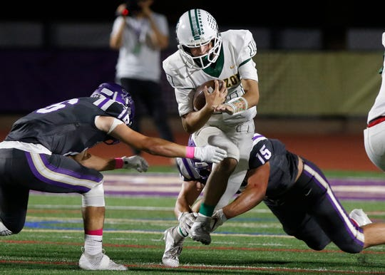 Horizon quarterback Jake Martinelli (10) runs between two Notre Dame Prep defenders during the first half of their game in Scottsdale, Friday, Oct. 11, 2019.