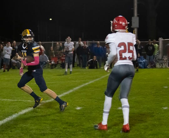 Port Huron Northern James DeLong walks into the end zone after catching a pass as Port Huron's Shaka Brown looks on during the fourth quarter of the Cross-Town Showdown Friday night.