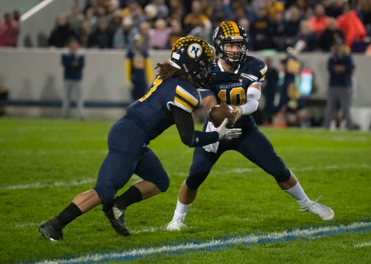 Port Huron Northern's Seth Klink hands off to Theo Ellis during the Cross-Town Showdown football game Friday night at Memorial Stadium.