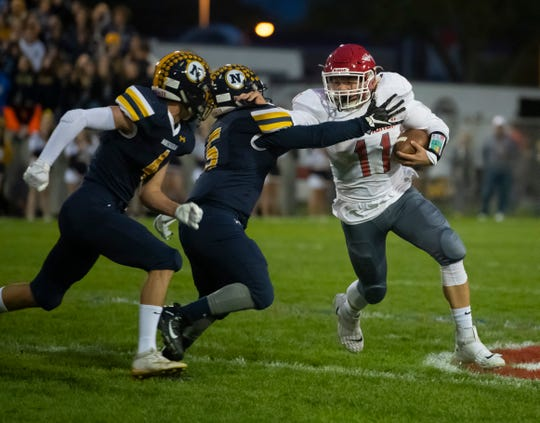Port Huron's Phil Mackay tries to run around Port Huron Northern's John Young and Owen Schumacher, left, during the first quarter of the Cross-Town Showdown Friday night at Memorial Stadium.