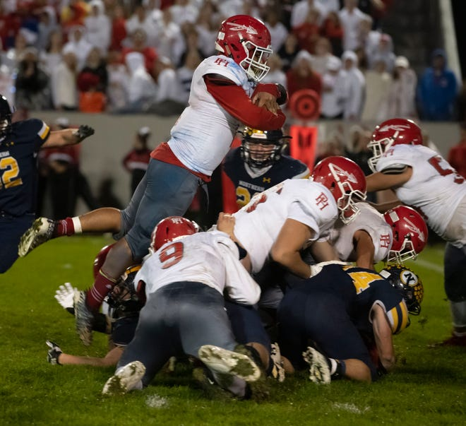 Port Huron's Caleb Collier jumps over a line for a short gain in the fourth quarter of the Cross-Town Showdown Friday night.