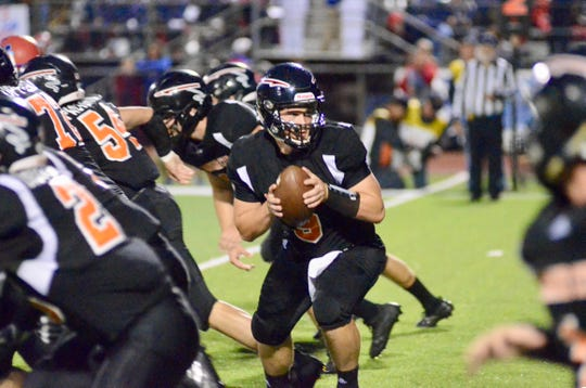 Marine City quarterback Colby Walker hands off the ball against St. Clair during a Macomb Area Conference-Silver football game on Friday, Oct. 11, 2019.