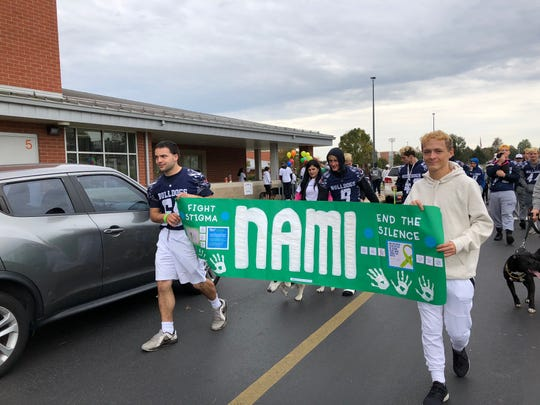 Senior Austin Rubio, 18, (left) and junior Ryan Green, 17 (right) carry the banner for the 10th annual Mental Health Awareness Walk for York-Adams chapter of the National Alliance on Mental Illness. The 2019 walk kicked off at 10 a.m. Saturday, Oct. 12 at West York Area Middle School.