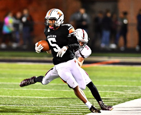 York Suburban's Donald Dent tries to break away from a Gettysburg tackler last Friday. The Trojans are 8-0 on the season.