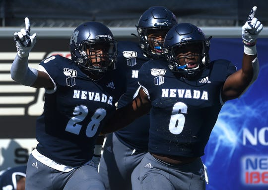 Nevada's Austin Arnold (28) celebrates with teammate Tyson Williams (6) after scoring on a pick six while taking on San Jose State during their football game at Mackay Stadium in Reno on Oct. 12, 2019.