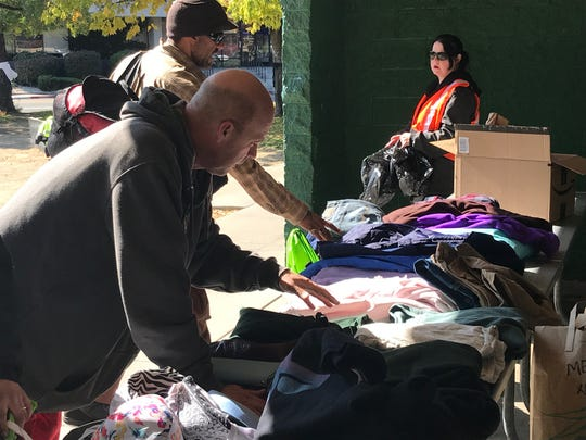 Homeless residents look through donated clothing at an event at Pickett Park, held on Saturday, Oct. 12, 2019.