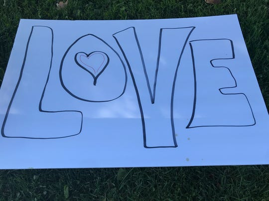 """A poster with the word """"Love"""" written on it is left on display at Pickett Park on Saturday, Oct. 12, 2019. Volunteers gathered to help the homeless residing in the area."""