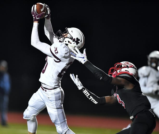 Aquinas' Gabriel Giannini, left, seals the game with an interception on a pass intended for Hilton's Tah-Jae Hill during a regular season game at Hilton High School, Friday, Oct. 11, 2019. Aquinas beat Hilton 42-33.