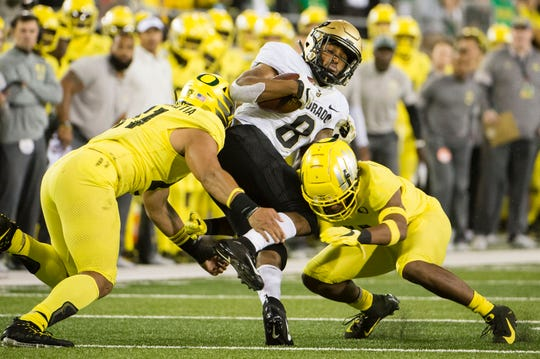 Oct 11, 2019; Eugene, OR, USA; Oregon Ducks linebacker Isaac Slade-Matautia (41) and safety Jevon Holland (8) tackle Colorado Buffaloes running back Alex Fontenot (8) during the first half at Autzen Stadium. Mandatory Credit: Troy Wayrynen-USA TODAY Sports