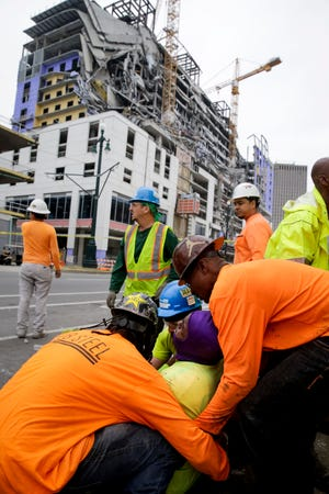 Workers are helped after a large portion of a hotel under construction suddenly collapsed in New Orleans on Saturday, Oct. 12, 2019. Several construction workers had to run to safety as the Hard Rock Hotel, which has been under construction for the last several months, came crashing down. It was not immediately clear what caused the collapse or if anyone was injured.
