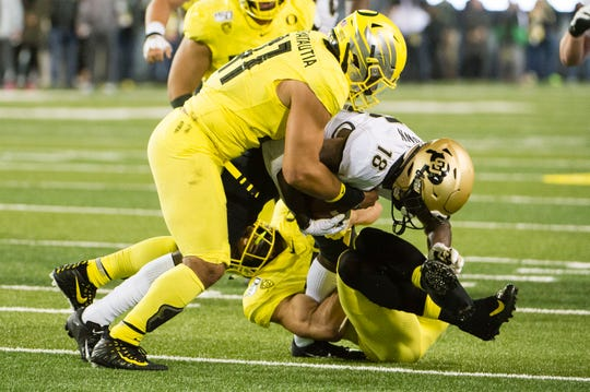 Oct 11, 2019; Eugene, OR, USA; Oregon Ducks linebacker Isaac Slade-Matautia (41) and linebacker Troy Dye (35) tackle Colorado Buffaloes wide receiver Tony Brown (18) during the first half at Autzen Stadium. Mandatory Credit: Troy Wayrynen-USA TODAY Sports