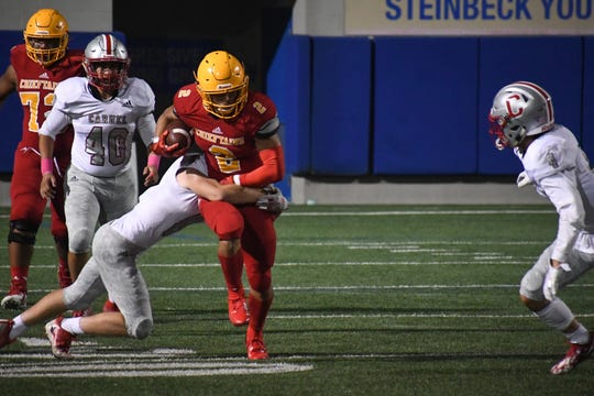 Palma running back Anthony Villegas (2) breaks through a tackle Friday night against Carmel. Oct. 11, 2019.