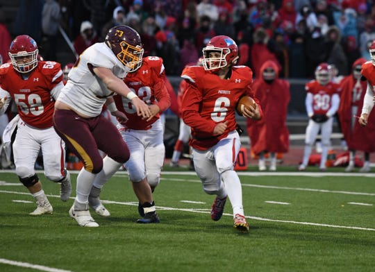 Sioux Falls Lincoln quarterback Tommy Thompson runs around the edge during the varsity matchup against Harrisburg on Friday night at Howard Wood Field.