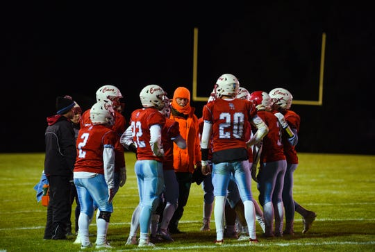 The Bon Homme Cavaliers head coach speaks to the team during a time-out while wearing blaze-orange gear to protect him from the cold during a game on Friday, October 11, in Tyndall.